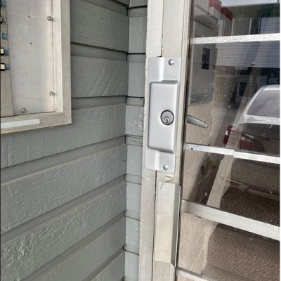Lock with door latch guard installed